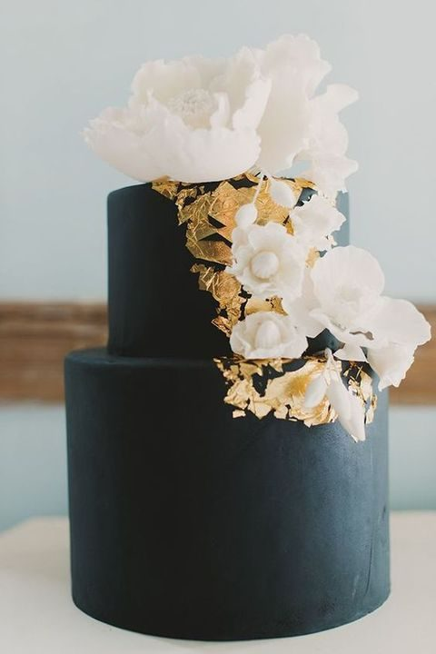 black cake with gold leaf decor and white flowers