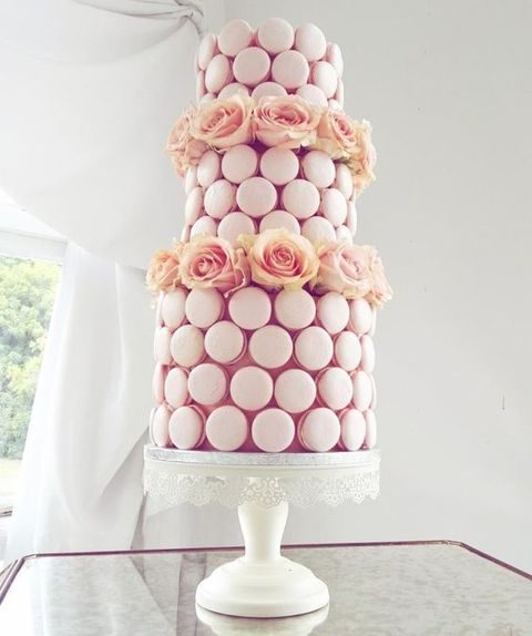 blush macarons shaped as a wedding cake and topped with flowers