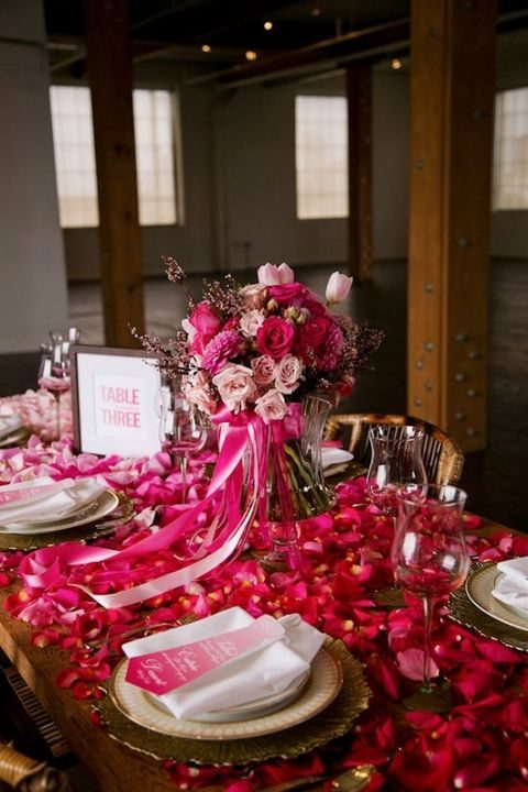 bold pink table decor covered with flower petals