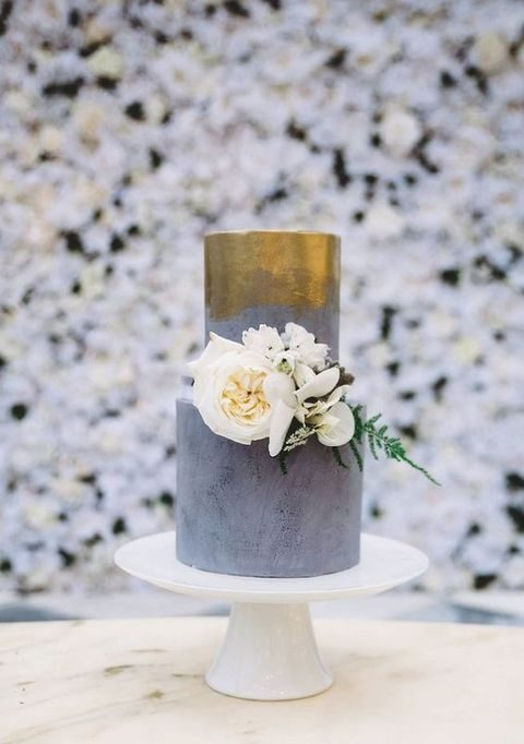 concrete-looking wedding cake with gold leaf and flowers