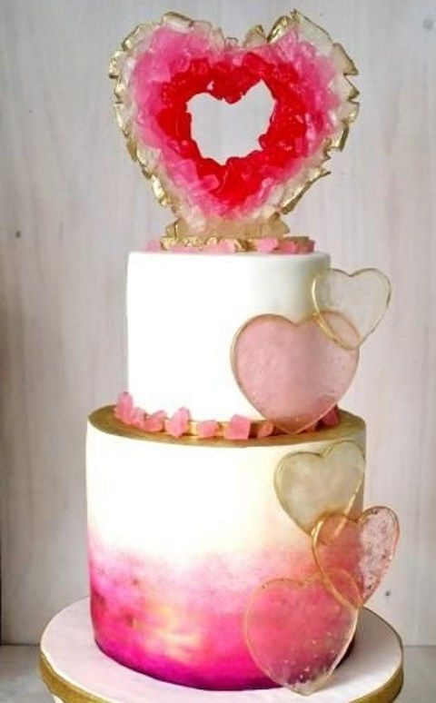 creative pink, gold and white wedding cake with a unique topper