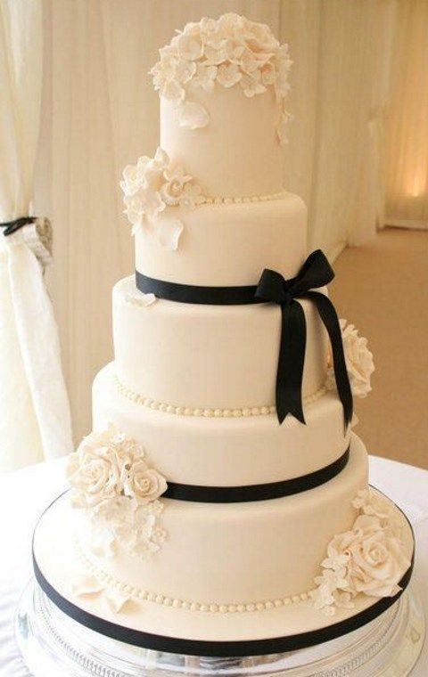 elegant tall wedding cake with black ribbon, sugar roses and hydrangeas