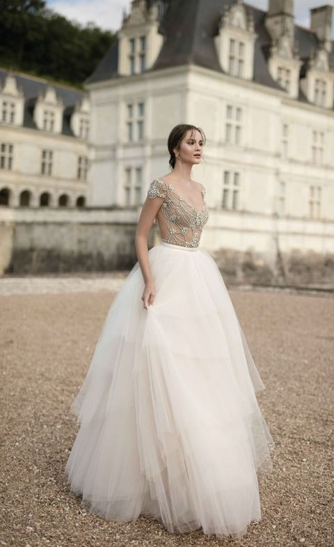 embellished nude bodice and a layered ivory tulle skirt