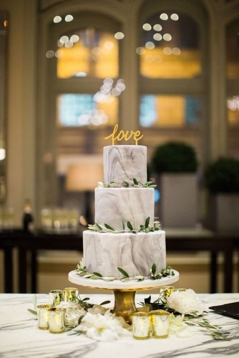 grey marble three-tier wedding cake decorated with fresh leaves