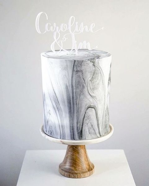 grey marbled wedding cake with a calligraphy topper
