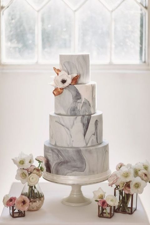 grey multi-tier wedding cake with an edible flower