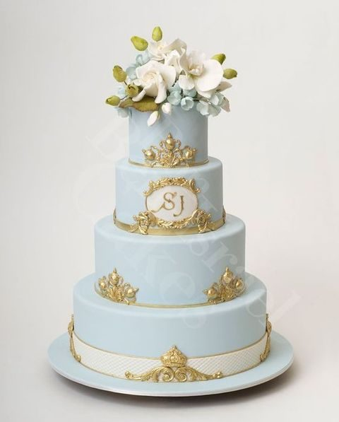 ice blue wedding cake with gold and orchids on top