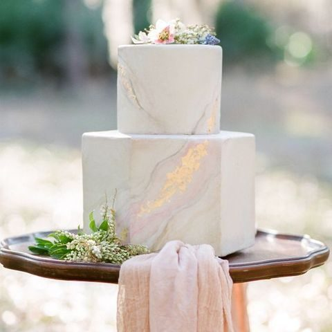 light marble two-tier cake with gold decor and flowers