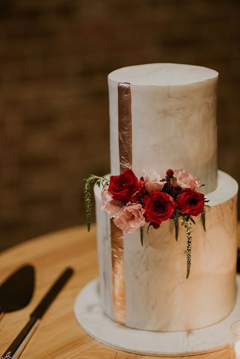 marble two tier wedding cake with a copper stripe and bold flowers