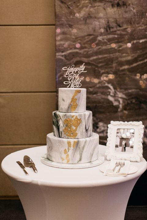 marbleized grey cake with gold leaf and a calligraphy topper