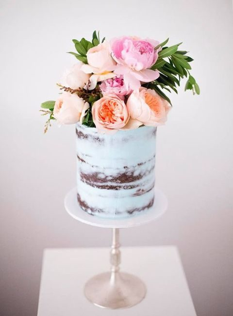 pale blue naked wedding cake with a fresh floral topper