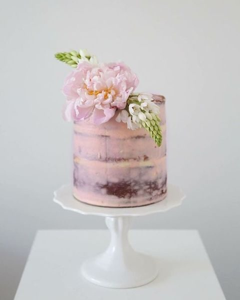 pale pink cake with fresh flower topper