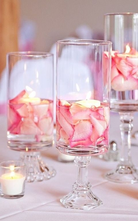 pink petals in glass goblets with floating candles