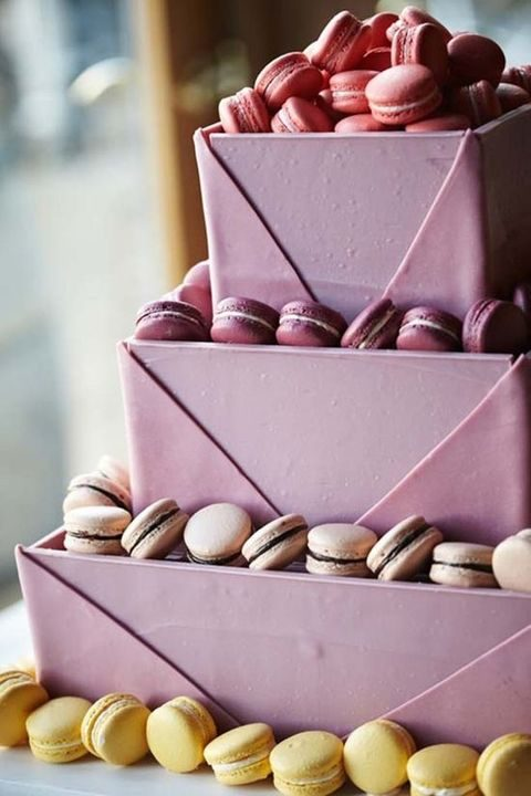 pink square cake topped with various macarons