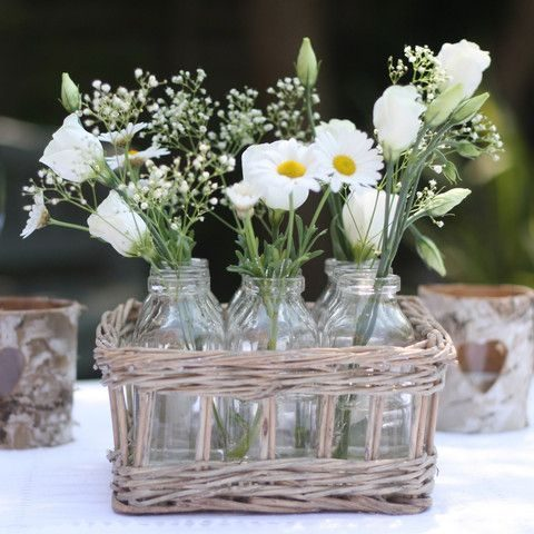 put bottles with flowers into a basket to get a rustic centerpiece