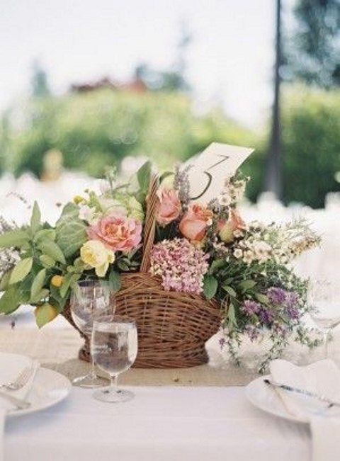 rustic basket centerpiece filled with flowers and greenery
