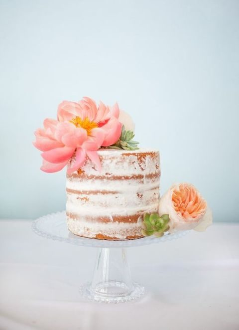 semi naked wedding cake topped with a large bloom