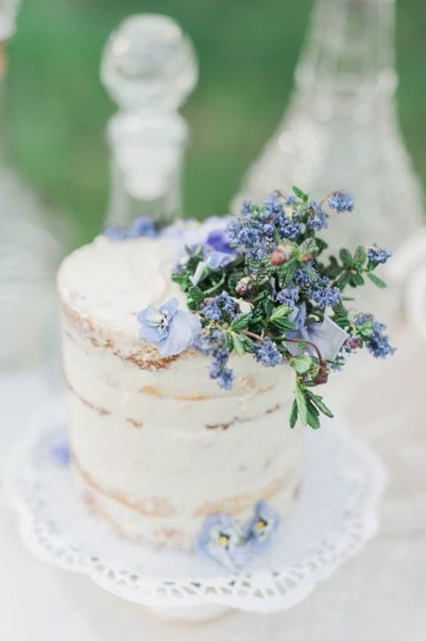 semi naked wedding cake topped with blue flowers