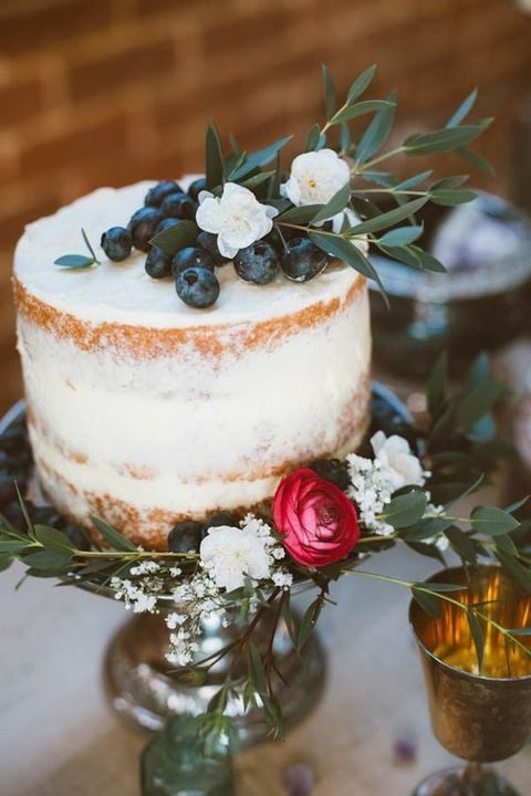 small naked wedding cake topped with blueberry and flowers