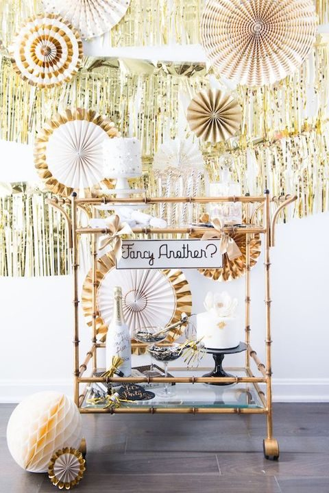 sparkling gold buntings and paper fans, cakes and champagne