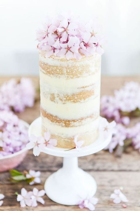 tall small wedding cake topped with cherry blossoms