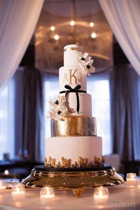 tall white and gold leaf cake with a black bow and white flowers