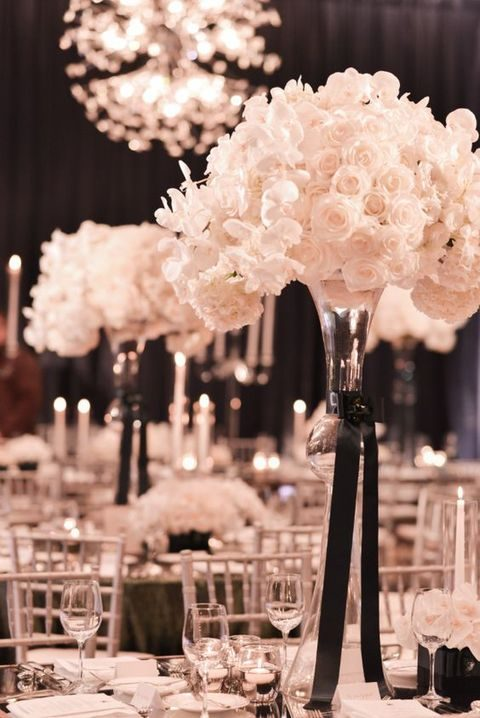transparent vase with a black bow and lush white roses