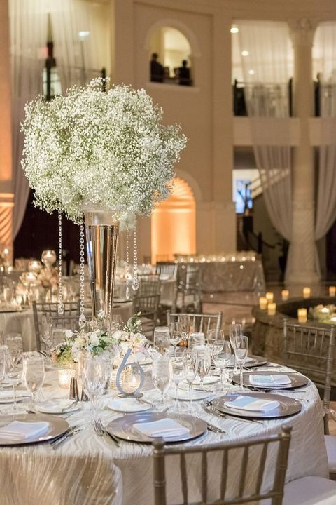 white and silver table decor with a baby's breath centerpiece