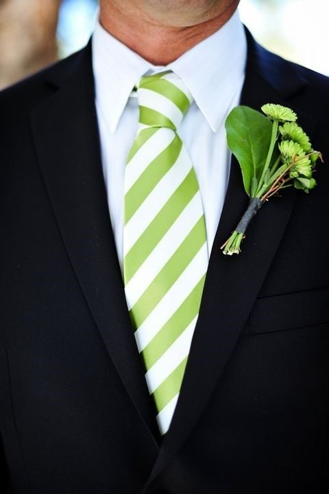 black suit with a white shirt and a greenery tie and boutonniere