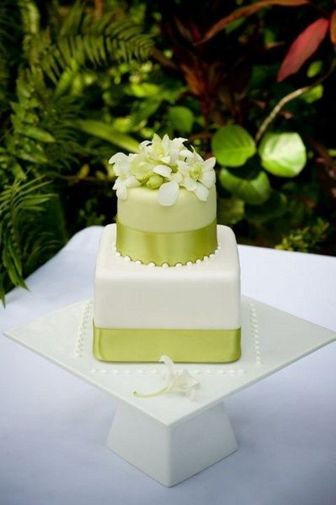 cake decorated with greenery ribbon and tropical flowers