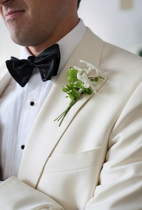greenery and white boutonniere for an elegant groom's look