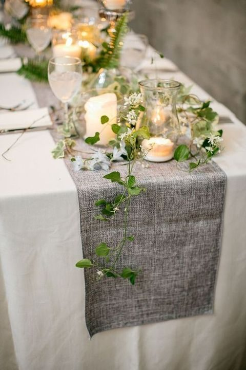 grey fabric table runner with candles and laves