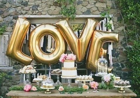 large gold balloons as a dessert table backdrop