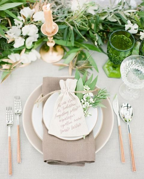 neutral place settting, a greenery table runner and gold cutlery