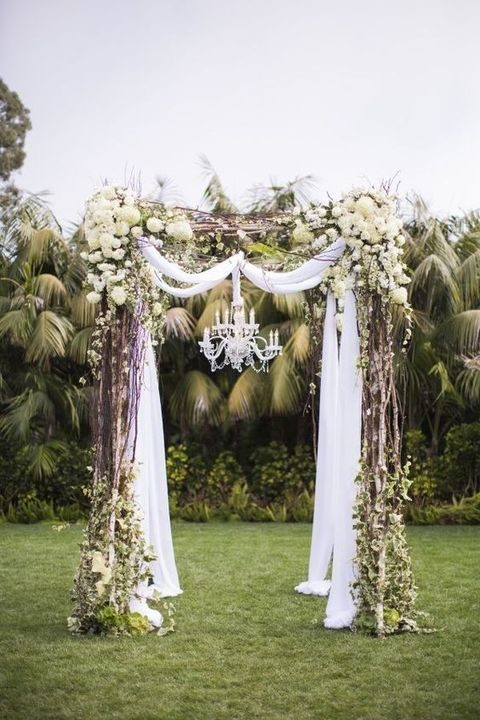 neutral wedding arch with ivory flowers and a crystal chandelier