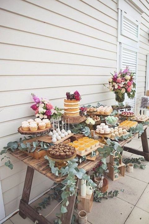 rustic dessert table decorated with lush florals and greenery