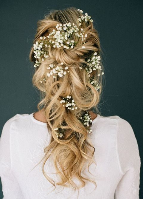 twisted and pinned curly hairstyle with baby's breath tucked in it