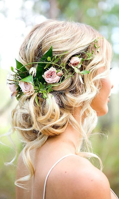 wavy messy updo with fresh flowers tucked into hair
