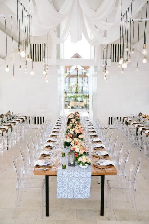 wedding venue with farm tables, pendant lighting, and clear ghost chairs