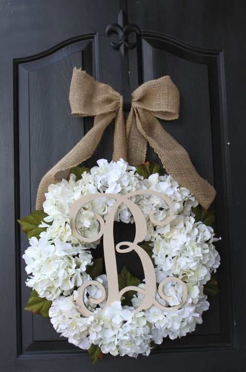white hydrangea floral wreath with a burlap bow and a monogram