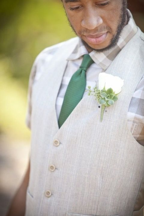 a beige vest, a checked shirt and a green tie