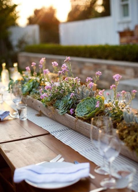 a wooden box with succulents and flowers as a table runner