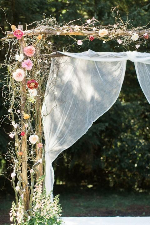ethereal wedding arch woven with flowers and fabric