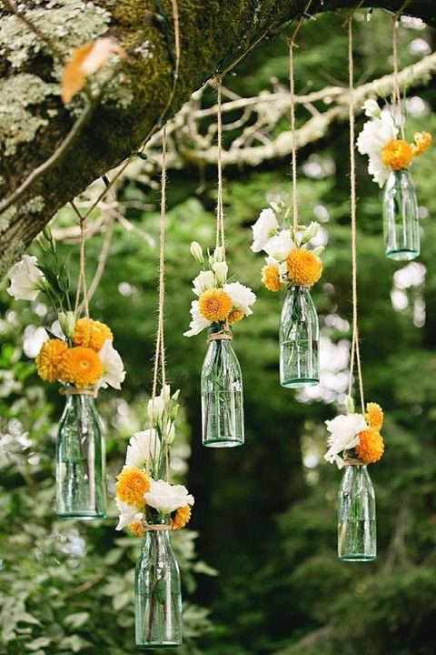 hanging glass bottles as vases with flowers
