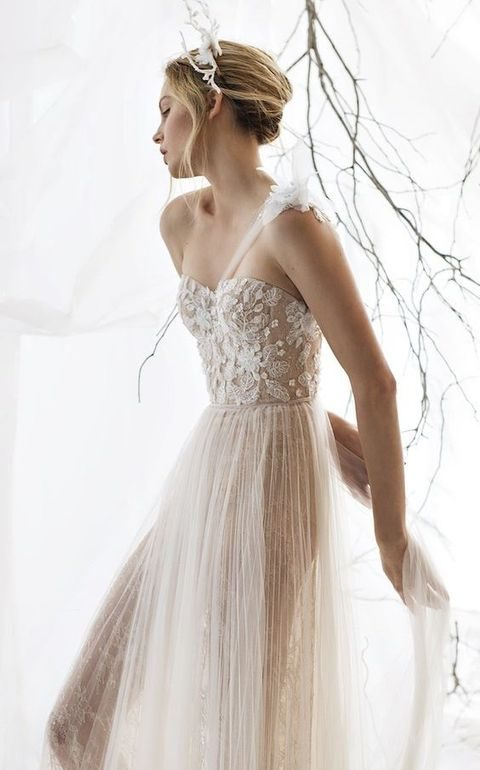 one-shoulder nude wedding dress with a floral applique bodice