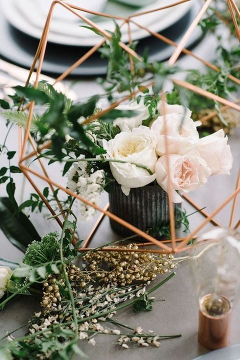 rustic and industrial centerpiece wwith blush florals and a geometric fixture