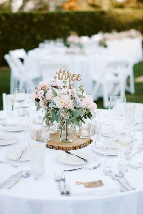 rustic centerpiece with a wood slice, blush florals and calligraphy