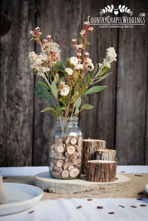 rustic centerpiece with wooden logs and silces inside the jar