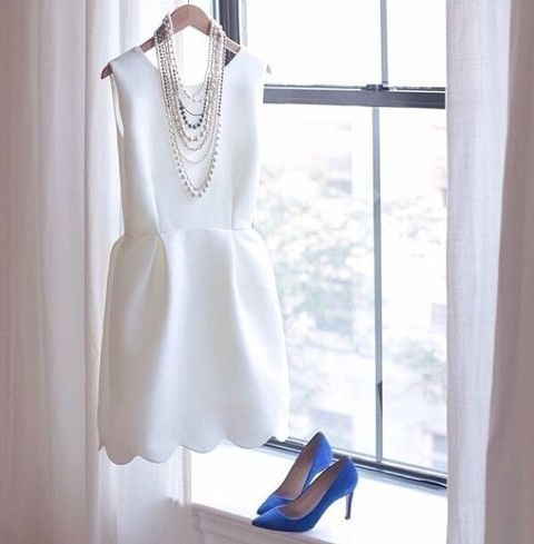 white sleeveless dress with a scallop edge and bold blue heels