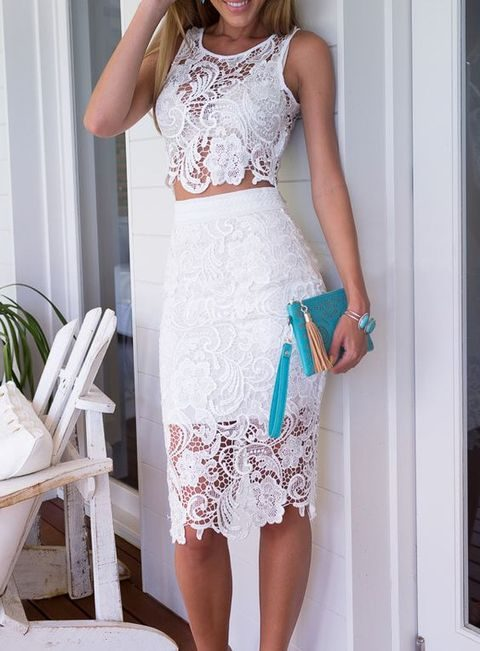 white sleeveless lace crop top and a knee-length skirt